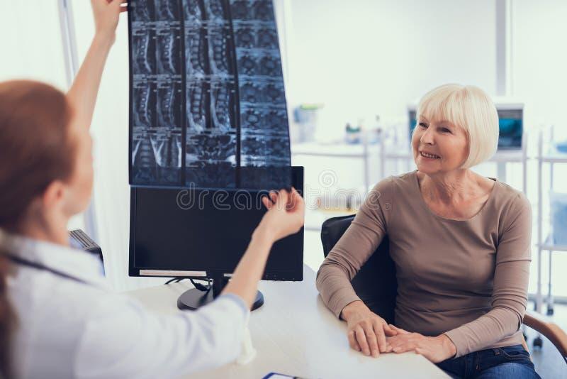 Lächelnde Frau erhält Röntgenstrahlergebnisse im Krankenhaus stockfoto