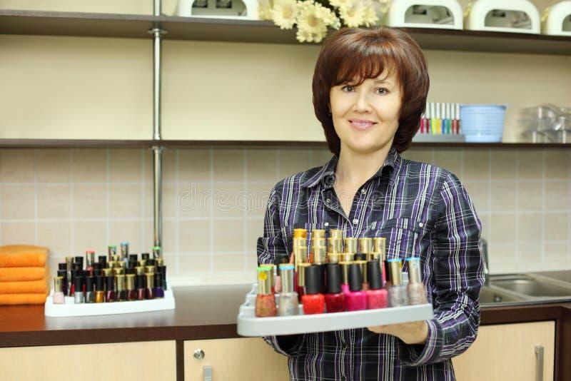 Lächelnde Frau hält farbigen Nagellack auf Standplatz an stockfotografie
