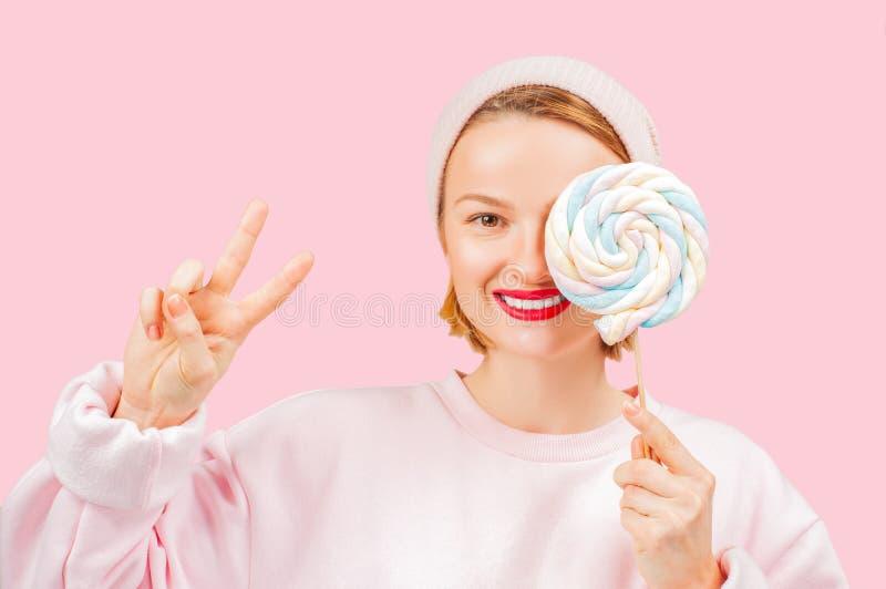 Lächelnde Frau hält Süßigkeitslutscher auf rosa Pastellhintergrund stockbilder