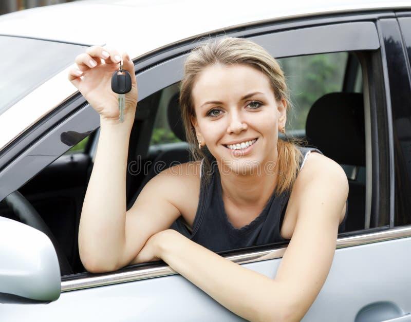 Lächelnde Frau im Auto, welches die Tasten zeigt lizenzfreies stockbild