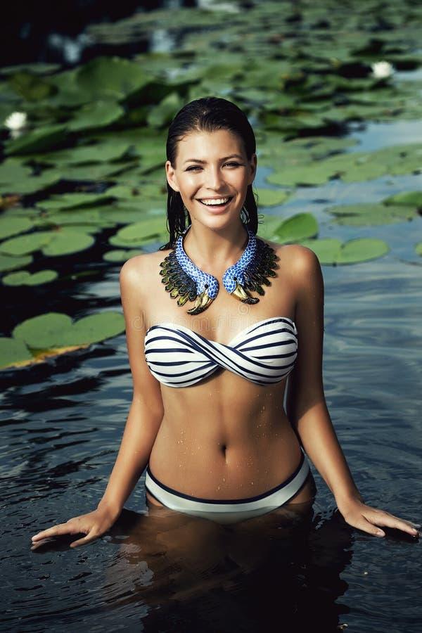 Lächelnde Frau im Badeanzug im Teich mit Seerosen lizenzfreies stockbild