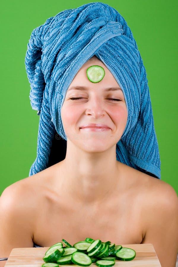 Lächelnde Frau im blauen Tuch und Schablone von der Gurke stockbild