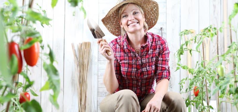 Lächelnde Frau im Gemüsegarten, Gartenkellewerkzeug im Kirschtomatenhintergrund zeigend lizenzfreie stockfotos
