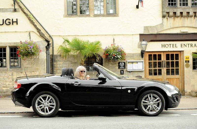 Lächelnde Frau im Sportauto stockfoto