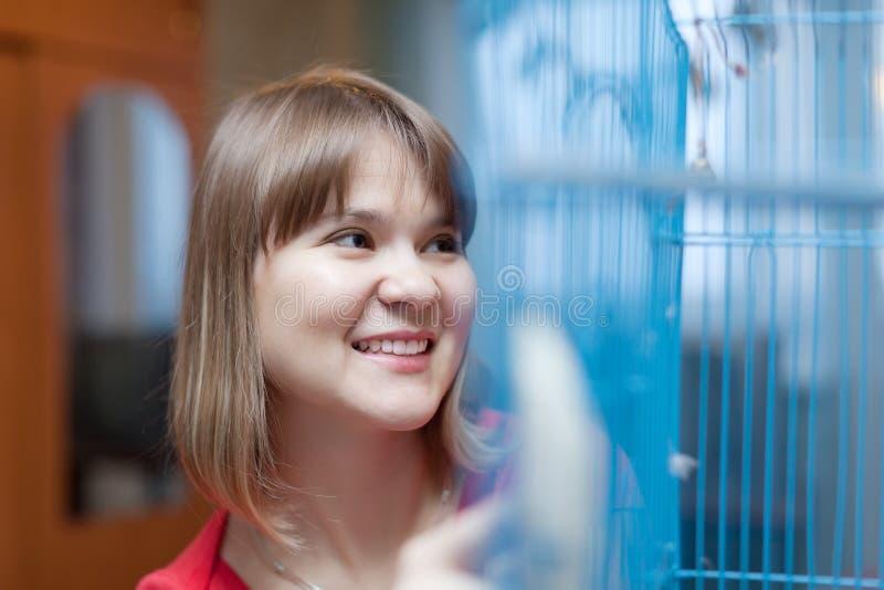 Lächelnde Frau am Käfig mit Haustieren stockfotos