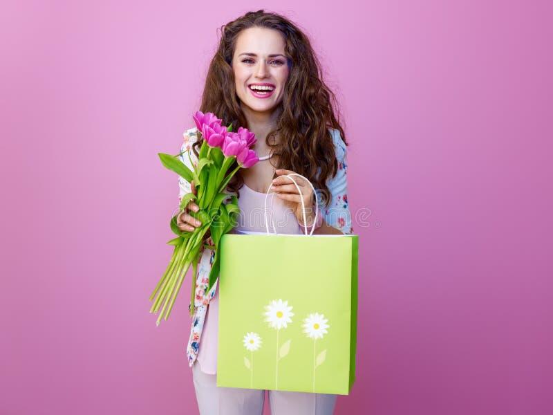 Lächelnde Frau mit Blumenstrauß von den Blumen, die Einkaufstasche zeigen lizenzfreie stockfotos