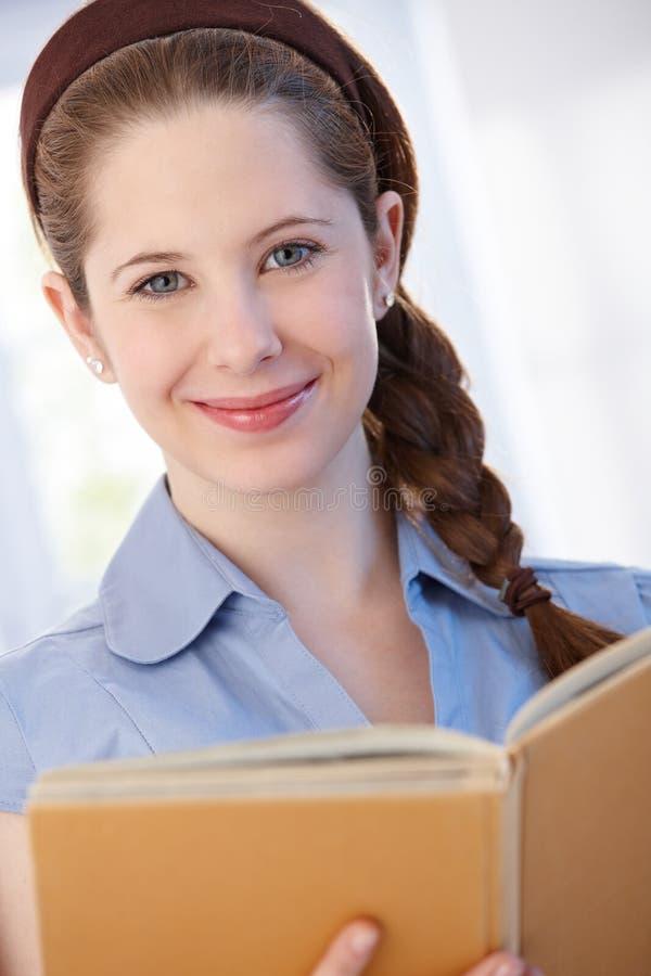 Lächelnde Frau mit Buch zu Hause lizenzfreies stockfoto
