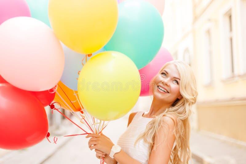 Lächelnde Frau mit bunten Ballonen lizenzfreies stockbild