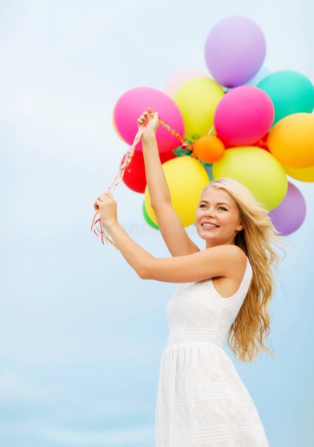 Lächelnde Frau mit bunten Ballonen draußen lizenzfreies stockfoto