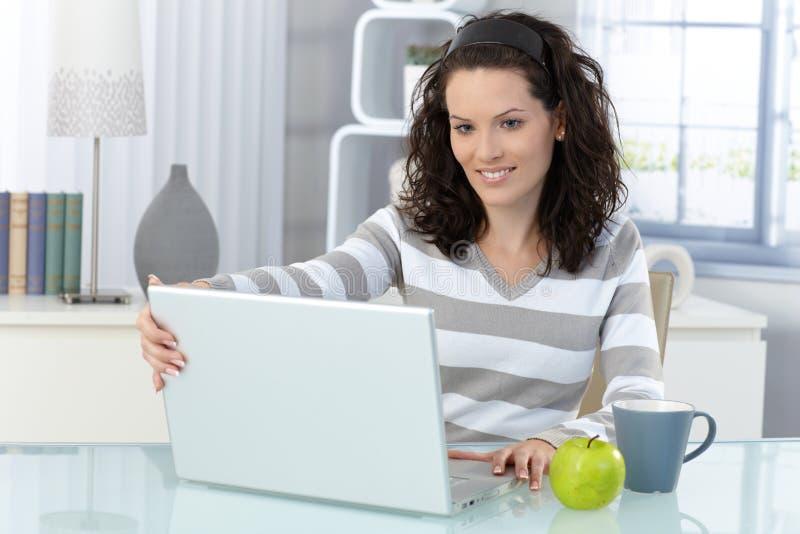 Lächelnde Frau mit Computer zu Hause lizenzfreie stockfotos