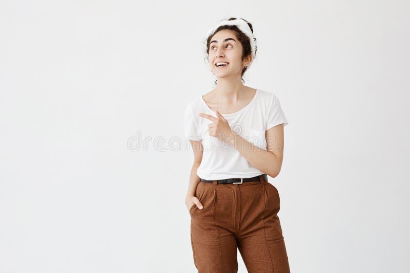Lächelnde Frau mit dem dunklen gewellten Haar im Brötchen in der zufälligen Kleidung, die gegen weißes Studio aufwirft, ummauern  lizenzfreie stockfotografie