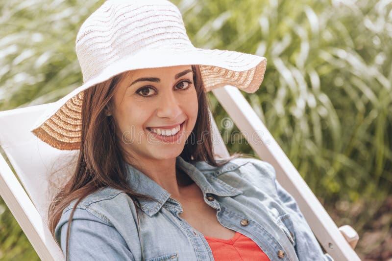 Lächelnde Frau mit dem Hut, der sich an entspannt, sunbed im Sommer stockbilder