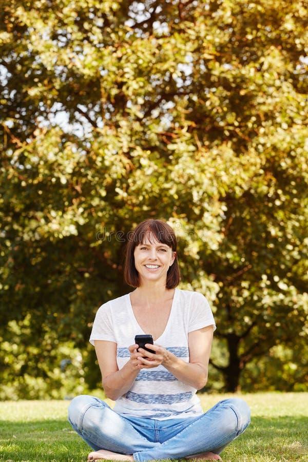 Lächelnde Frau mit dem intelligenten Telefon, das im Gras sitzt stockbild