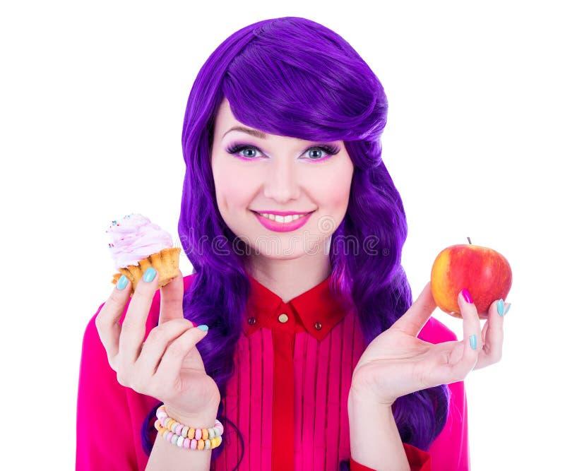 Lächelnde Frau mit dem purpurroten Haar, das Apfel- und Kuchenisolat hält lizenzfreies stockfoto
