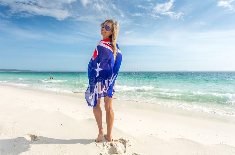 Lächelnde Frau mit der australischen Flagge eingewickelt um ihren Körper sonnig stockfoto