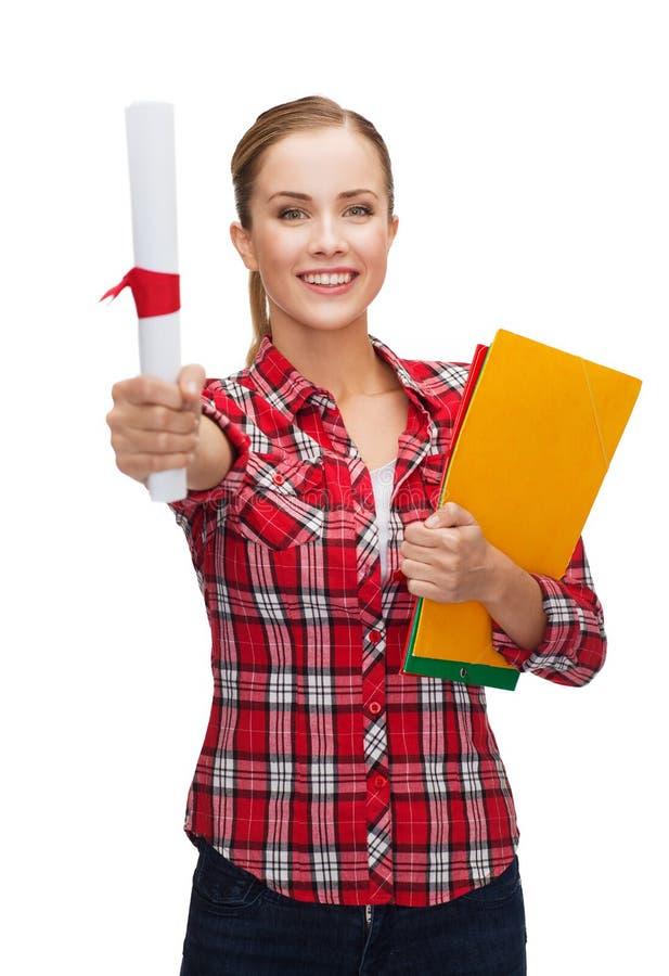 Lächelnde Frau mit Diplom und Ordnern lizenzfreie stockbilder