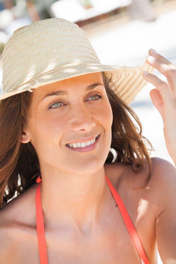 Lächelnde Frau mit einem Strohhut stockfotos