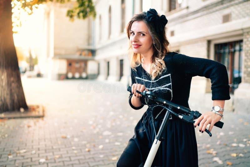 Lächelnde Frau mit elektrischem Trittroller an einem schönen Herbsttag stockbild