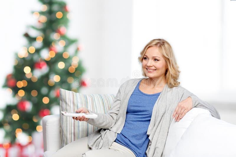 Lächelnde Frau mit Fernsehfernbedienung am Weihnachten lizenzfreies stockfoto