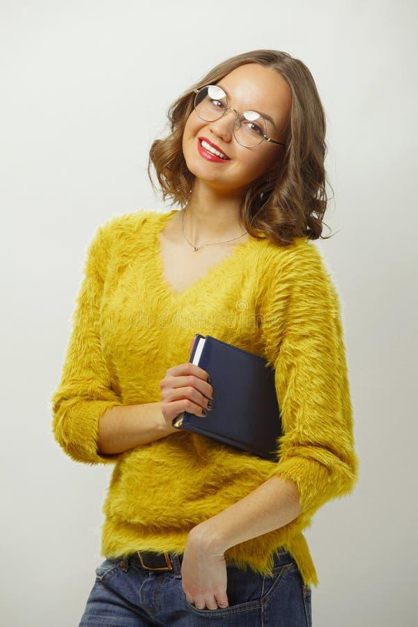 Lächelnde Frau mit hellem Auftritt und nettem Ausdruck, tragend ringsum die Schauspiele und farbige Kleidung und betrachten stockfotografie