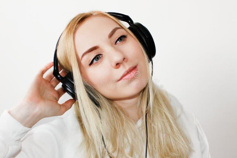 Lächelnde Frau mit in Kopfhörern hörend Musik auf weißem Hintergrund, Draufsicht Attraktives lustiges Modell in den roten Gläsern lizenzfreie stockfotografie