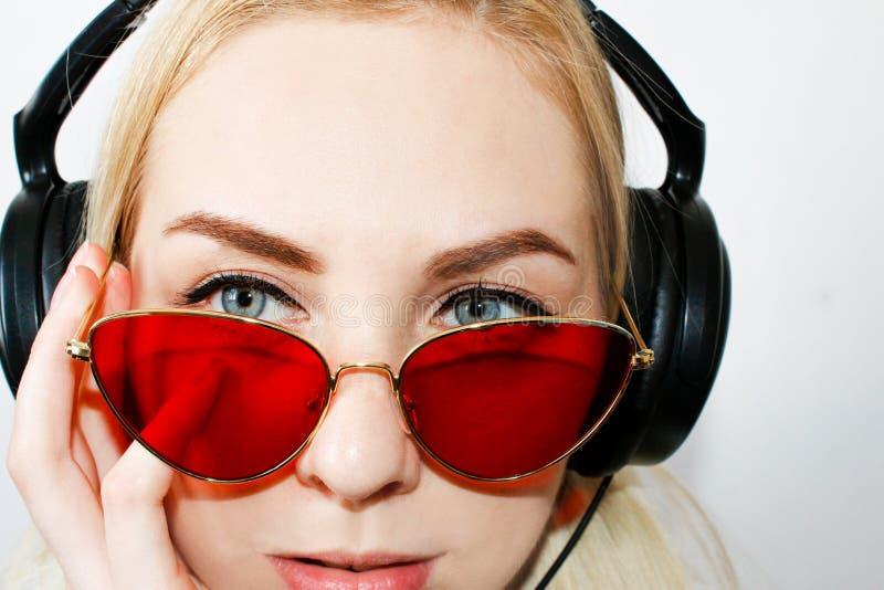 Lächelnde Frau mit in Kopfhörern hörend Musik auf weißem Hintergrund, Draufsicht Attraktives lustiges Modell in den roten Gläsern lizenzfreies stockfoto
