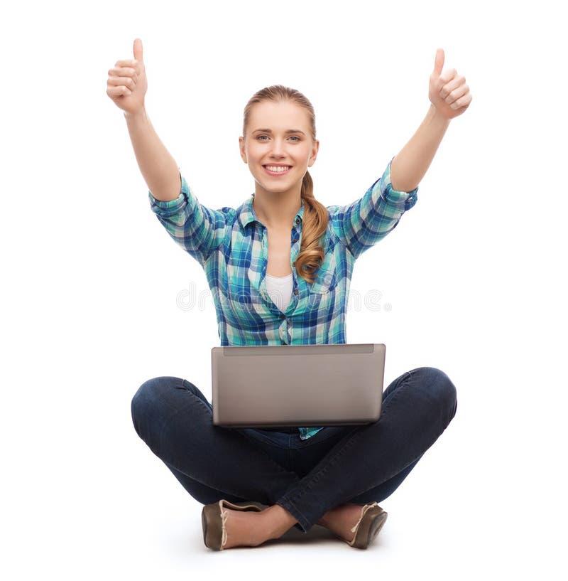 Lächelnde Frau mit Laptop und sich zeigen Daumen lizenzfreies stockbild