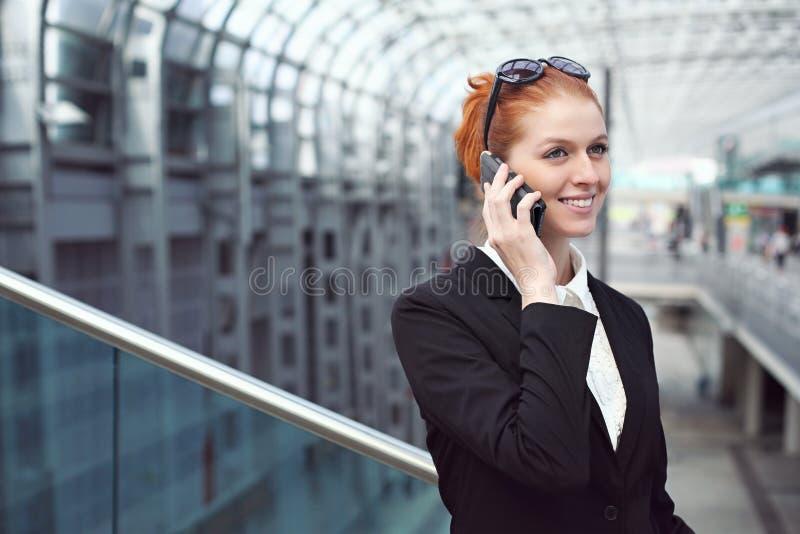 Lächelnde Frau mit Mobiltelefon an der Bahnstation stockfotografie