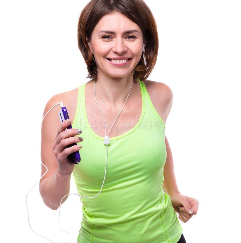 Lächelnde Frau mit Mobiltelefon und Kopfhörern auf Training lizenzfreies stockbild