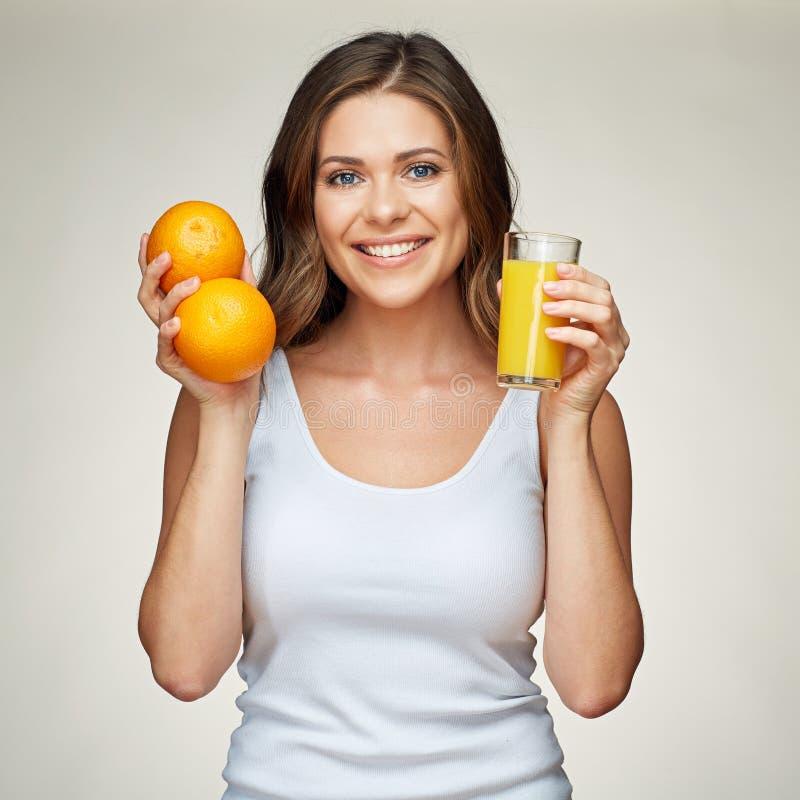 Lächelnde Frau mit orange Frucht und Saft lokalisierte Porträt lizenzfreie stockfotos