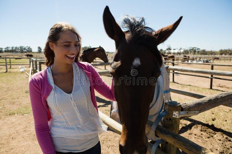 Lächelnde Frau mit Pferd an der Ranch lizenzfreie stockbilder