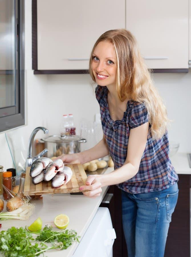 Lächelnde Frau mit rohen Seebarschfischen lizenzfreie stockfotos
