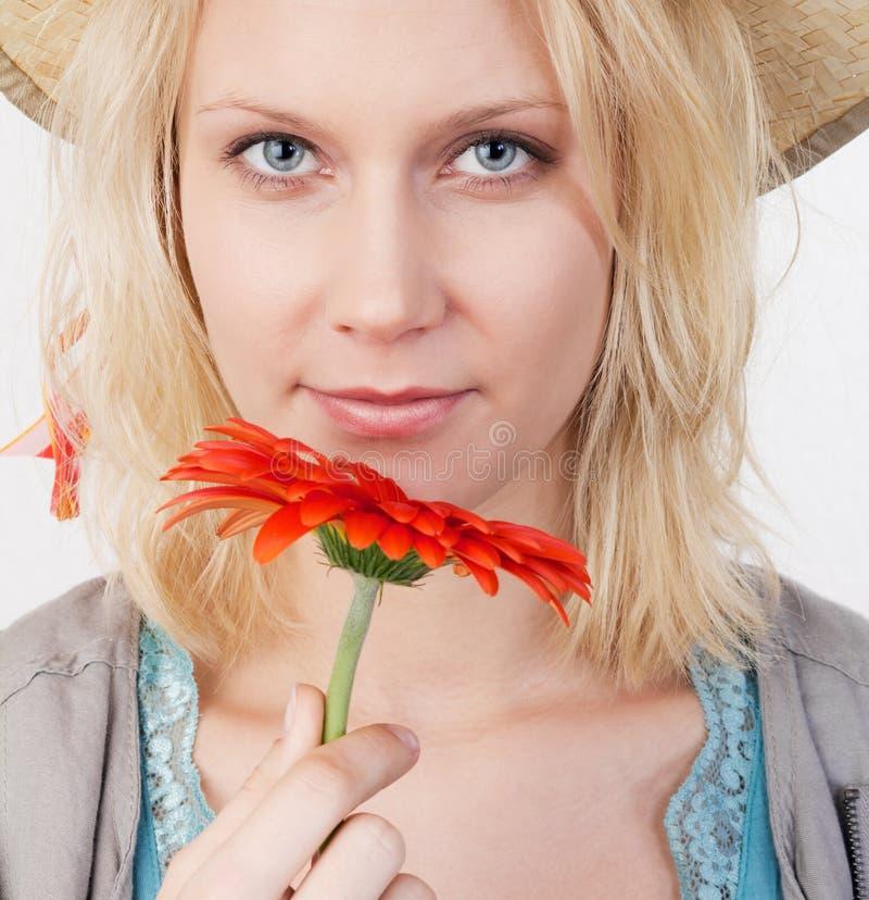 Lächelnde Frau mit roter Blume lizenzfreies stockbild