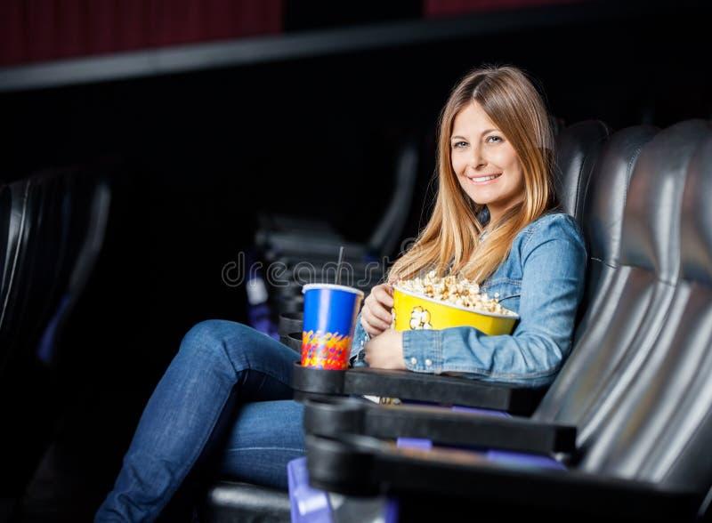 Lächelnde Frau mit Snäcken am Kino-Theater lizenzfreies stockfoto