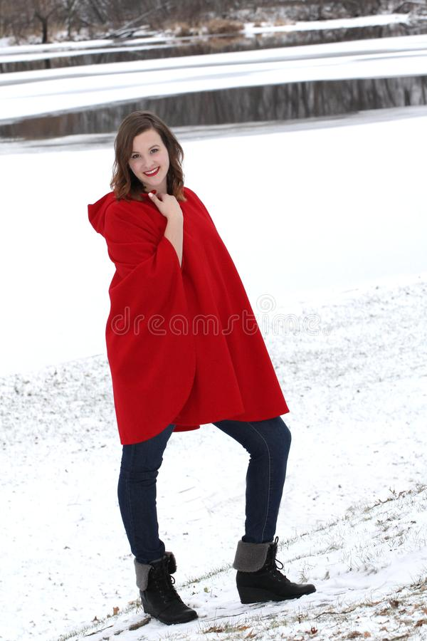 Lächelnde Frau steht draußen nahe einem schneebedeckten Flussufer im Weinlesewollkap stockbilder