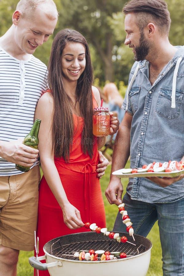 Lächelnde Frau und Freunde, die shashliks während des Gartenfests im Sommer grillen stockfoto