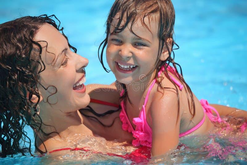 Lächelnde Frau und kleines Mädchen badet im Pool lizenzfreies stockbild