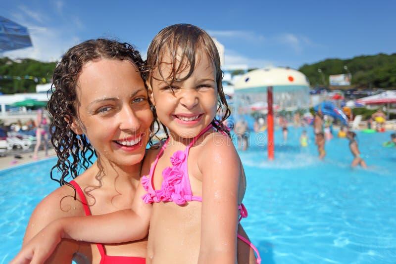Lächelnde Frau und kleines Mädchen, die im Pool baden lizenzfreies stockbild