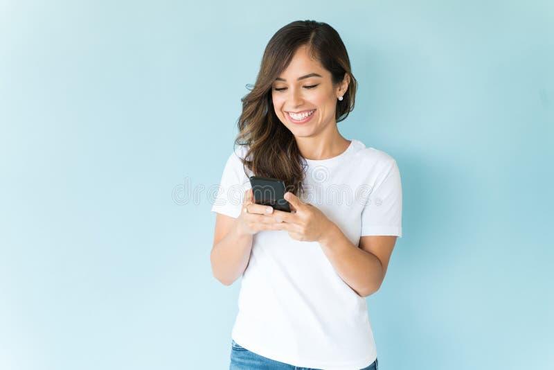 Lächelnde Frau unter Verwendung des Handys auf farbigem Hintergrund lizenzfreie stockfotos