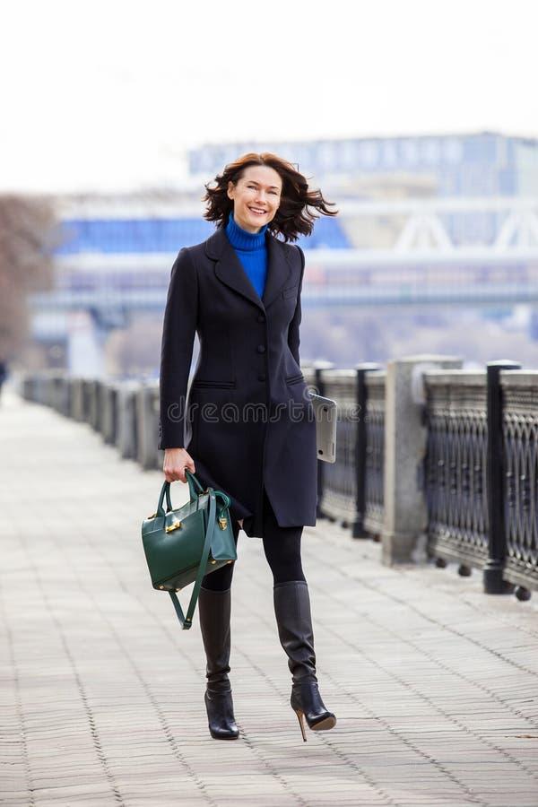 Lächelnde Frau von mittlerem Alter in einem dunklen Mantel geht auf Damm stockbilder