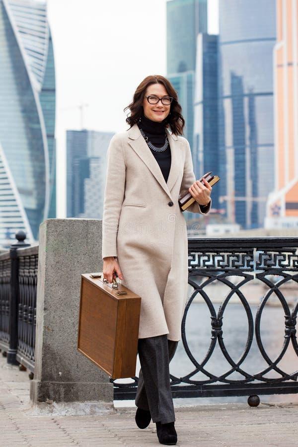 Lächelnde Frau von mittlerem Alter in einem hellen Mantel lizenzfreie stockbilder