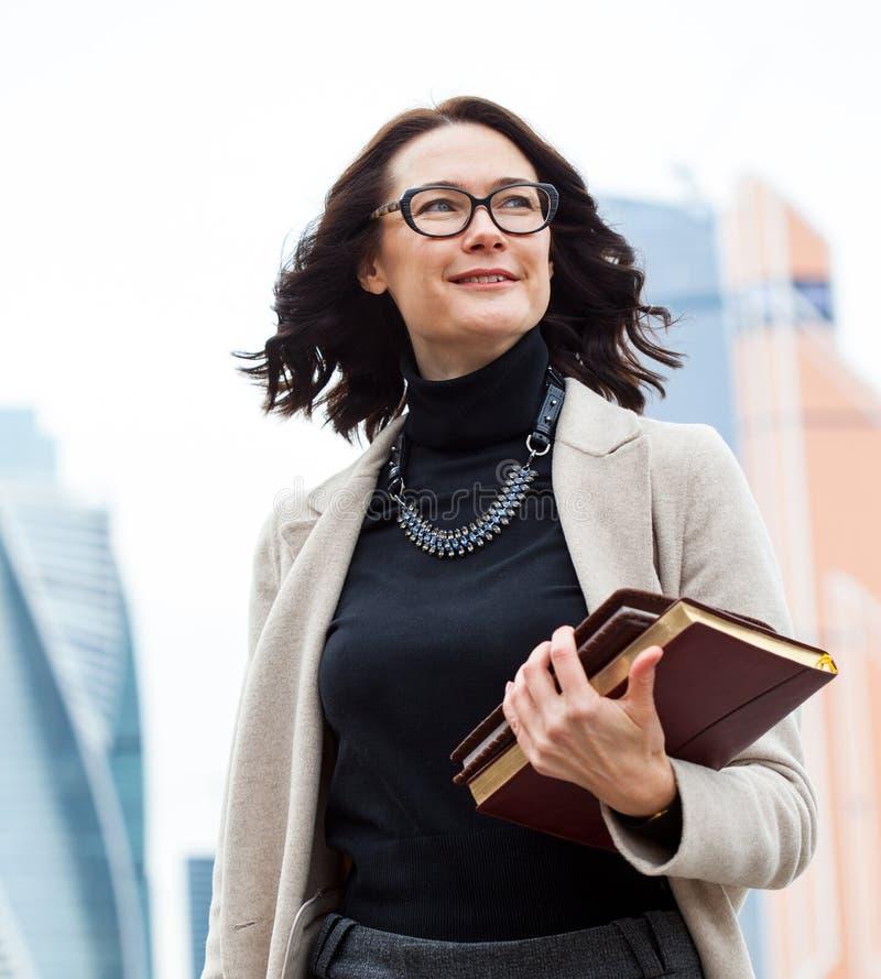 Lächelnde Frau von mittlerem Alter mit Büchern stockfotografie