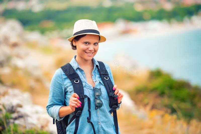 Lächelnde Frau, Wanderer, der auf Weg, Berge mit Rucksack geht Reisen und Trekking auf Küstenlinie stockbilder