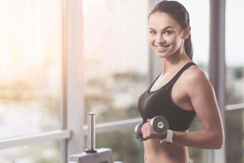 Lächelnde Frau, welche die Dummköpfe in der Turnhalle hält lizenzfreie stockfotografie
