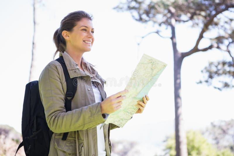 Lächelnde Frau, welche die Karte hält stockfotografie