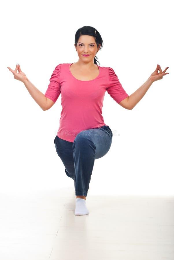 Lächelnde Frau in Yogastellung lizenzfreie stockbilder