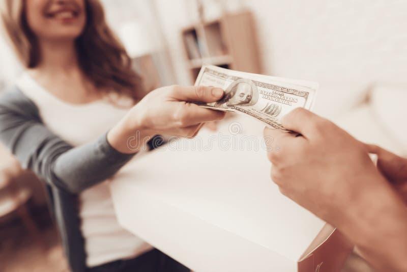 Lächelnde Frau zahlt Kurier Delivery in den Dollar stockfoto