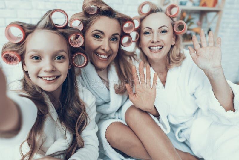 Lächelnde Frauen in den weißen Bademäntel, die Selfie nehmen stockfoto