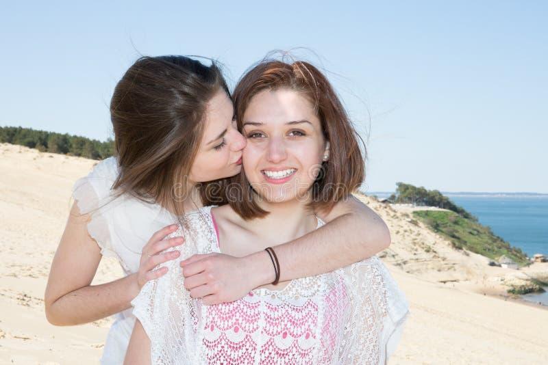 Lächelnde Frauen, die auf Seehintergrund umarmen lizenzfreies stockbild