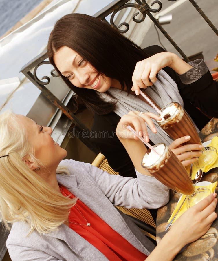Lächelnde Frauen, die einen Kaffee trinken stockfotografie